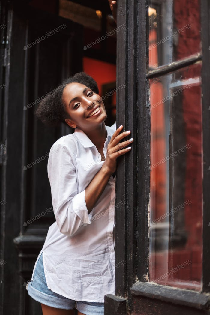 schön lächelnd afrikanische Mädchen mit dunkel lockiges Haar in weiß shi