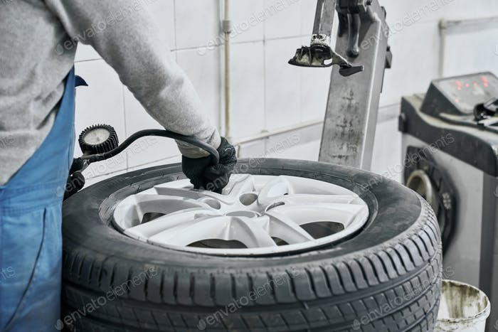 Auto mechanic inflating tire and checking air pressure