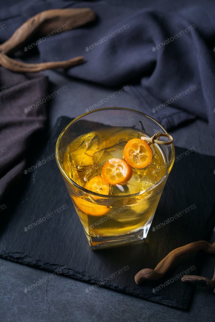 Glass of strong alcohol, whiskey, ice, kumquat on a table