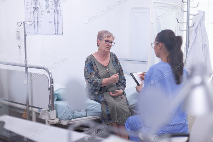 Nurse taking notes on clipboard consulting old woman