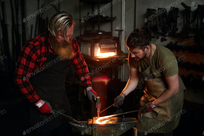 Blacksmiths forging iron