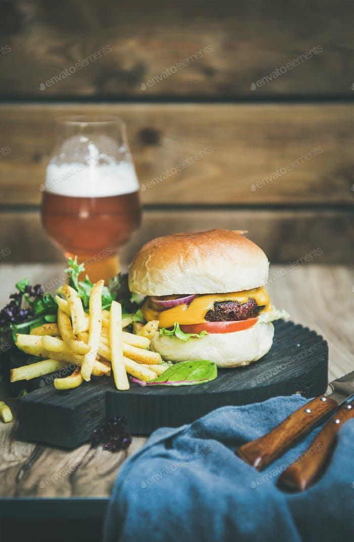 Classic burger dinner with french fries, salad, beer