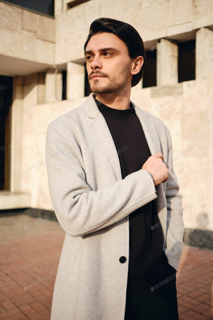 Young handsome stylish man in coat confidently looking away outdoor