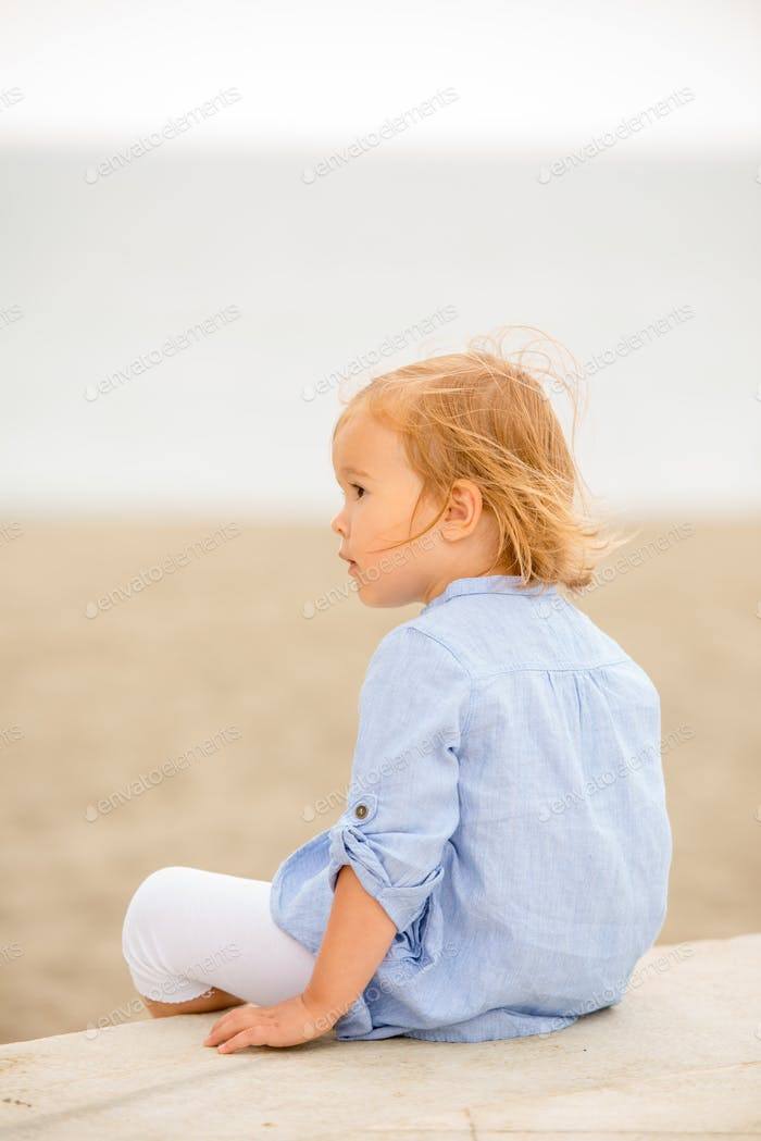 Pretty blond girl sitting overlooking the sea