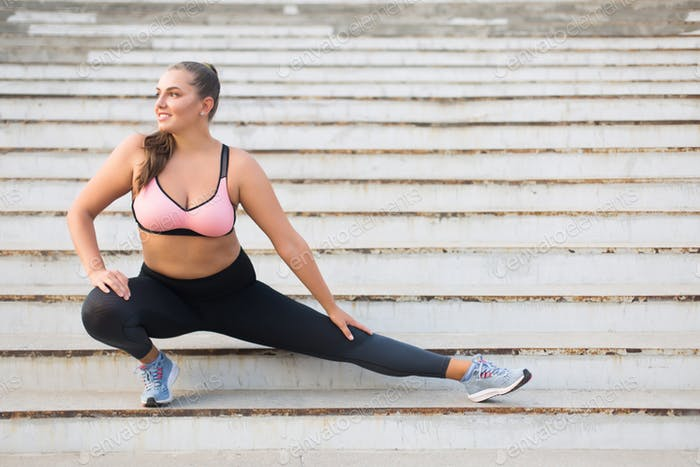 Beautiful smiling plus size girl in sporty top and leggings doin