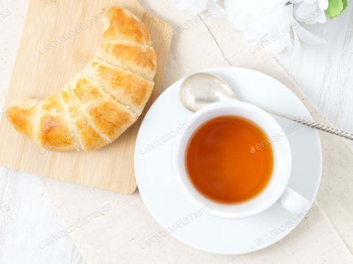 Cup of tea, flowers and fresh baked puff pastry on a white table. Delicious croissants