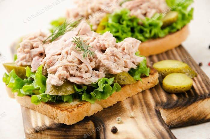 Homemade tuna salad sandwiches on cutting board with pickles aside