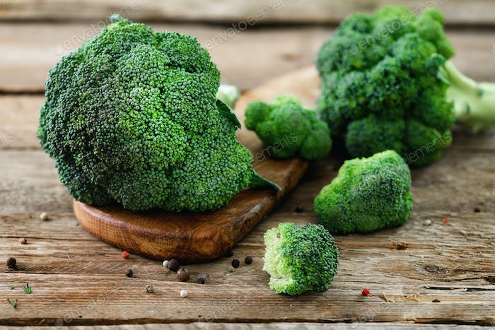 Fresh organic broccoli on wooden table close up