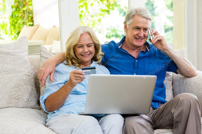 Senior couple using laptop while talking on phone at home