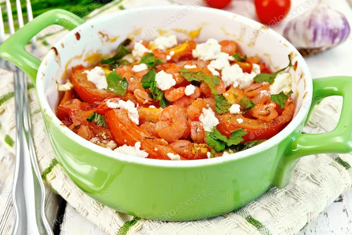 Shrimp and tomato with feta in green pan on light board