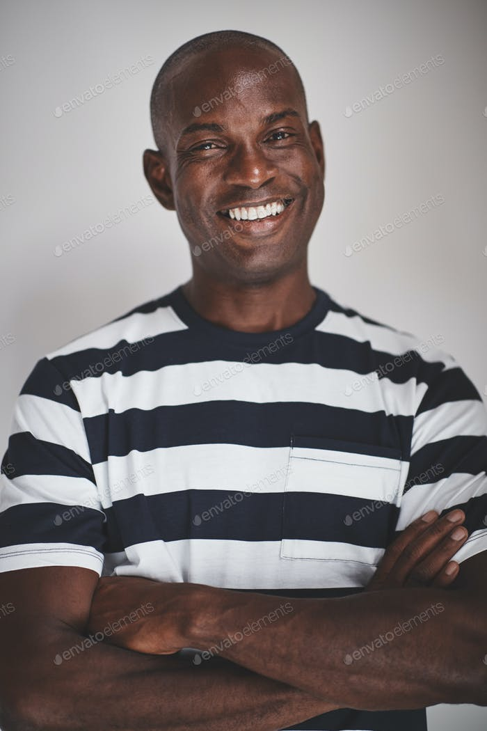 Smiling African entrepreneur standing against a gray background