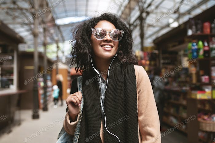 Portrait of beautiful girl with dark curly hair in sunglasses walking around city