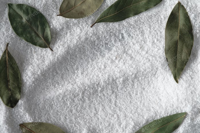 Salt with frame of bay leaf background
