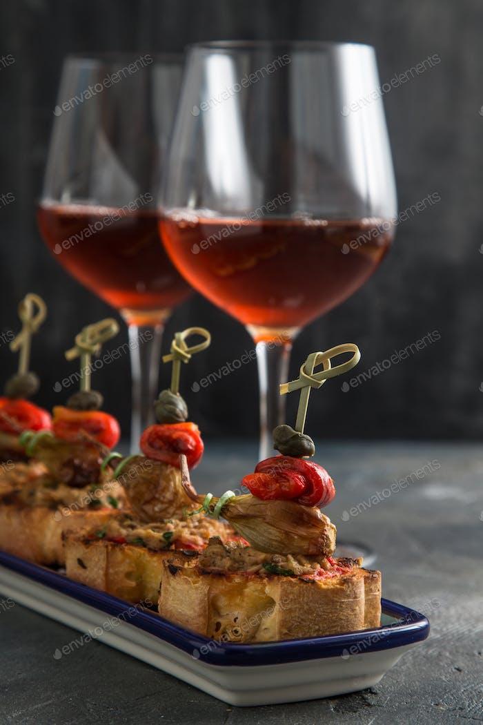 spanish tapa pinxtos with tuna, peper, onion and oregano. Wine on background