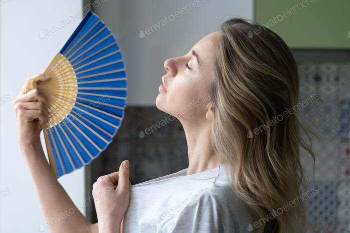 Overheated woman in t-shirt using wave fan suffer from heat sweating, cools herself, feels sluggish