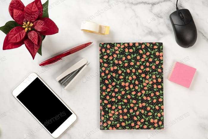 Office supplies on a marble desk with mobile phone, notebook, post it, red flower