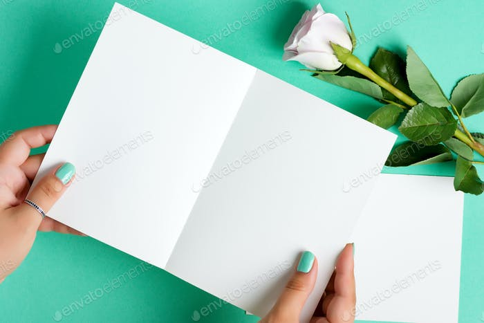 Woman's hands are holding empty mock-up paper sheet for writing letter above pastel turquoise