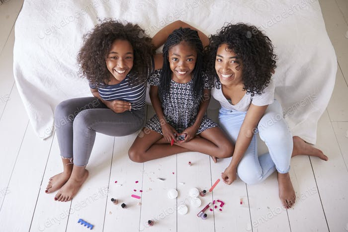 Three Teenage Sisters Giving Each Other Makeover In Bedroom