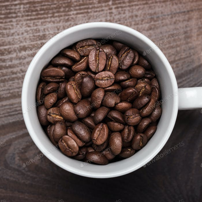 Cup Of Coffee Beans On Brown Wooden Background