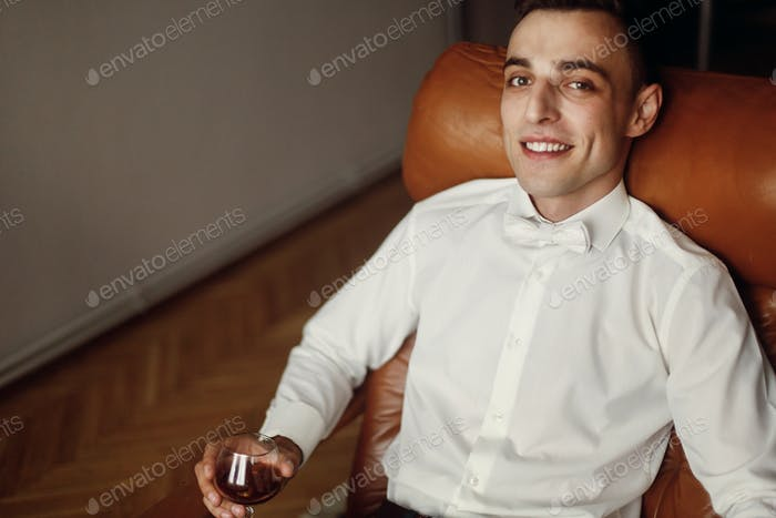 Handsome groom in white shirt sitting in luxury leather chair and holding whiskey
