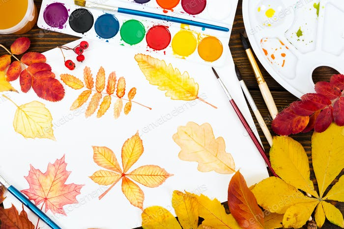 Drawing with watercolor autumn leaves on wooden background. Top