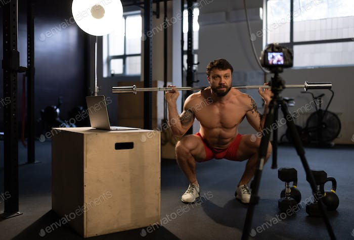Sportsman doing squats with bar in front of camera