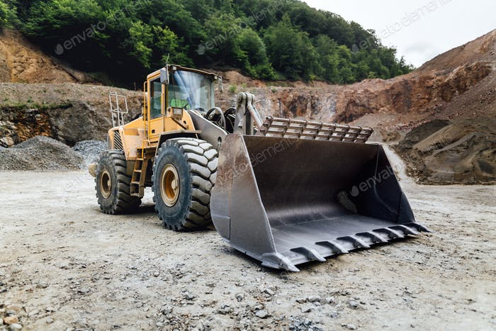 empty wheel loader machine loading gravel. Industrial machinery working at ore quarry
