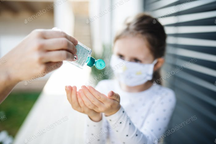 Small girl with face mask outdoors at home. Corona virus and quarantine concept
