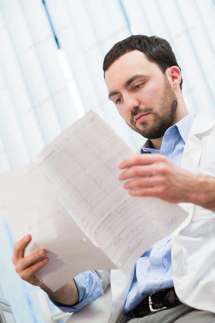 Männlicher Arzt überprüft etwas in seinen Papieren. Medizinische Versorgung, Versicherung, Rezept, Papier