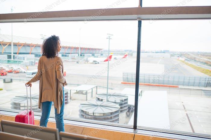 black woman looking trough airport window