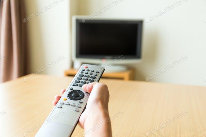 TV-Fernbedienung in der Hand
