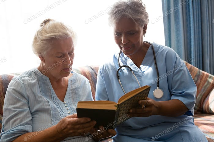 Doctor with senior woman reading book while sitting on sofa