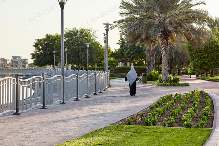 Arab woman walks in the park along the alleys of the city park
