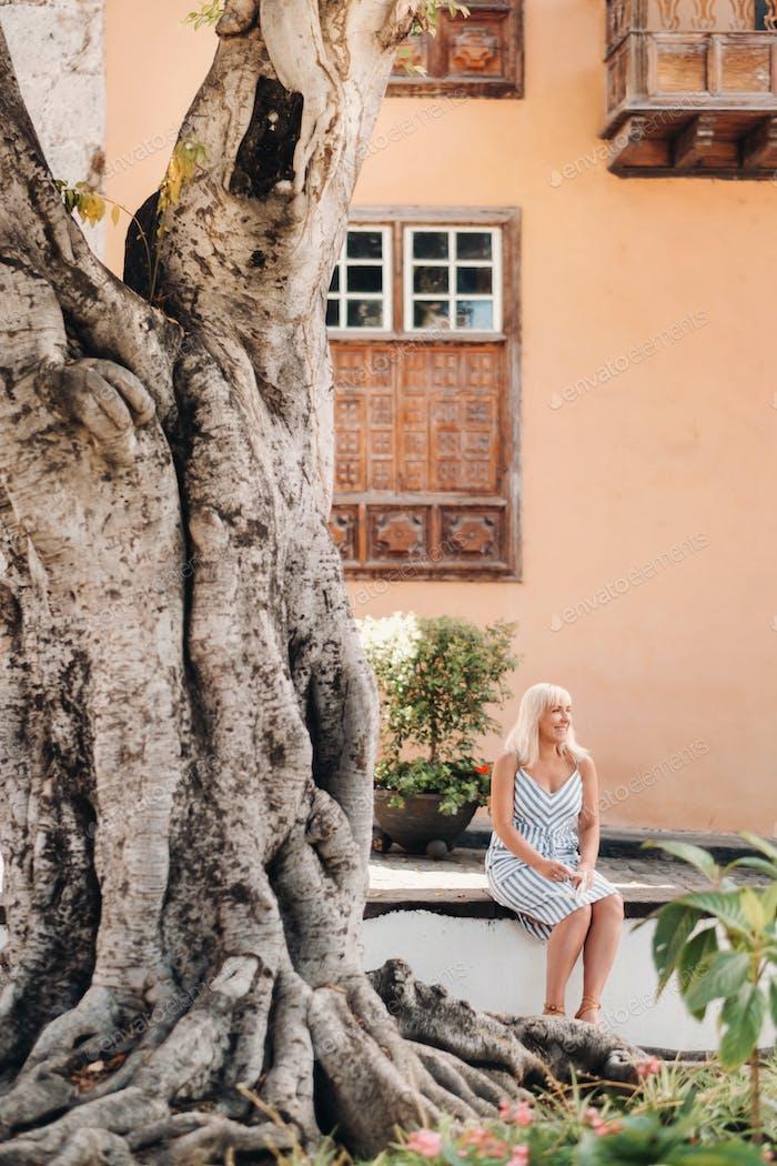 una mujer rubia en un vestido de verano se sienta en la calle del casco antiguo de Garachico en la isla de