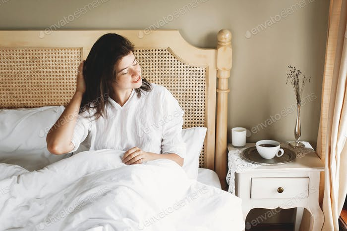 Beautiful happy young woman lying on bed in the morning