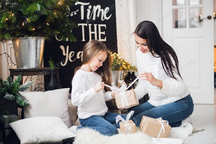 Merry Christmas and Happy Holidays! Cheerful mom and her cute daughter girl opening a Christmas