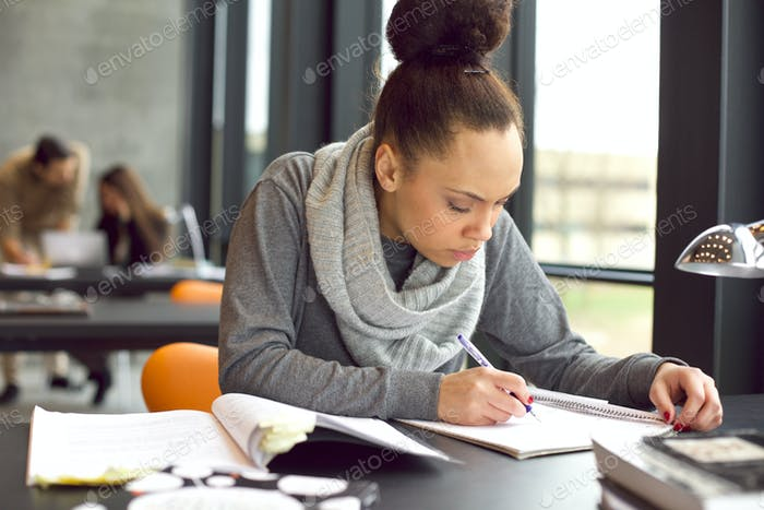 Young african american woman taking notes for her study