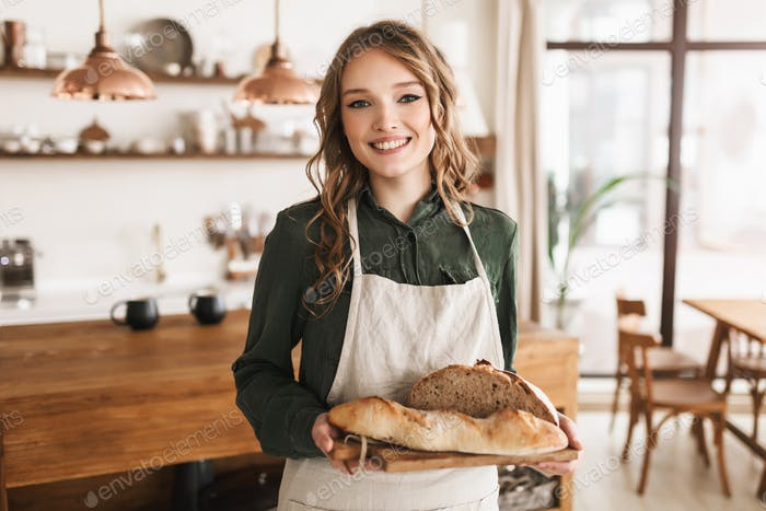 Young pretty smiling woman in white apron holding bread on board in hands happily looking in camera