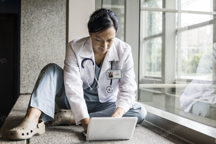 Asian woman doctor working on a lap top in a hospital  hallway.