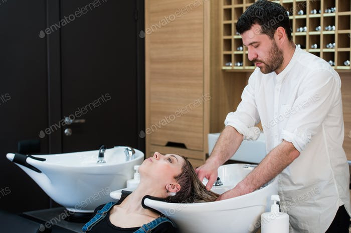 Handsome hairdresser washing female hair with concentration. He is holding a water tap. Woman