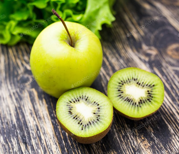 Fresh kiwi, apples and almonds on wooden background. Concept of healthy lifestyle