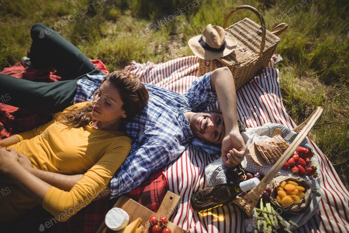 Portrait of happy young man lying with girlfriend on blanket
