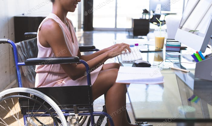 Young disabled businesswoman working on computer at desk