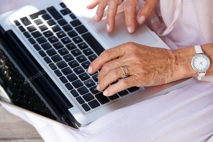 ältere Frau, die auf Laptop-Computer tippt