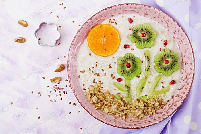 Tasty and healthy oatmeal porridge with kiwi, pomegranate and nuts.