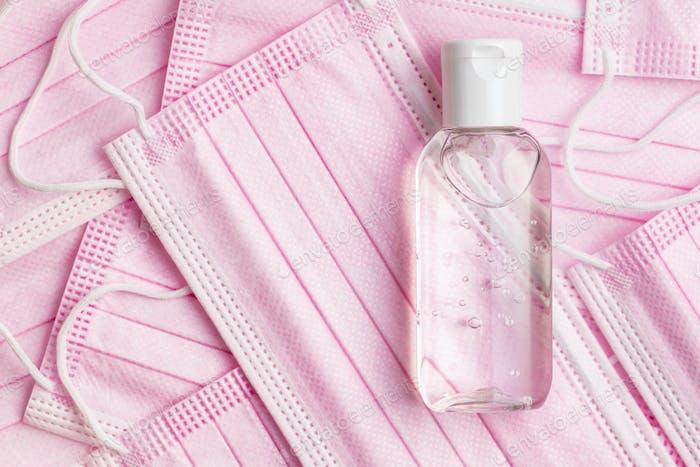 Antibakterielle Handgel und rosa Gesichtsmasken