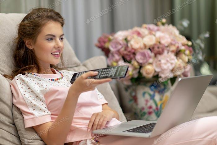 Lächelnde Frau auf der Couch ändern tv-Kanal zu Hause in der lebenden
