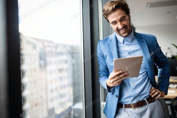 Portrait of businessman smiling while using digital tablet