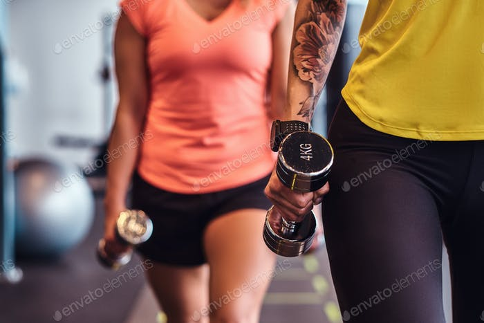 Two fitness girls in sportswear doing lunges with dumbbells in the modern gym.
