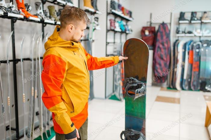 Man choosing snowboard, shopping in sports shop